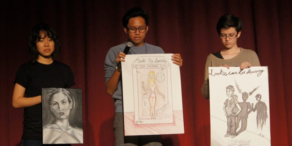 Three Mililani High School students present their artwork.